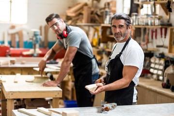 Happy carpenters working in workshop