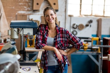 Happy female carpenter standing in workshop