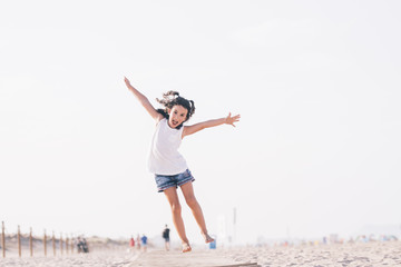 Little happy girl jumps on the sand of the beach looking at camera.