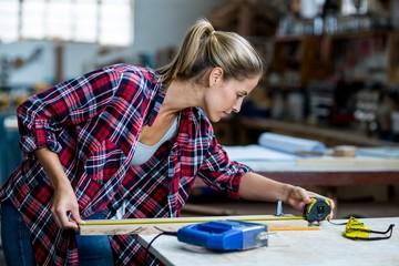 Female carpenter measuring length of wooden plank