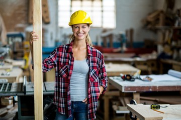 Portrait of female carpenter standing with wooden plank
