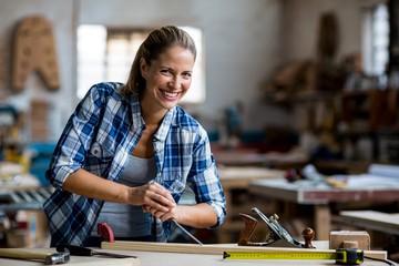 Female carpenter using chisel on wooden plank