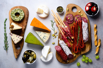 Cutting board with cold smoked meat, prosciutto, salami, assortment of cheeses, bread sticks, capers, olives on grey stone background. Cheese and meat appetizer. Top view, copy space, flat lay