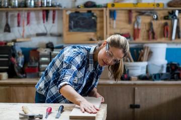 Female carpenter measuring a wooden plank