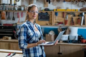 Female carpenter using laptop