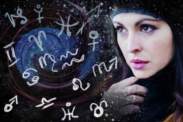 The woman watches on magic zodiac signs and symbols of planets