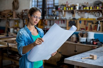 Female carpenter looking at a blueprint