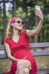 Young woman in a red retro dress taking a selfie, posing in front of her cell phone camera