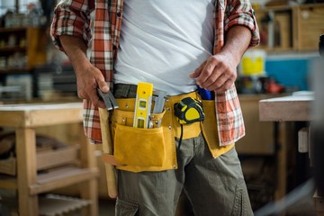 Carpenter removing hammer from tool belt