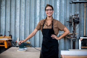 Portrait of female carpenter standing with polishing machine