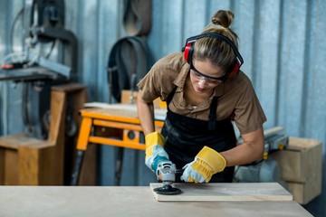 Female carpenter polishing a wooden plank with polishing machine