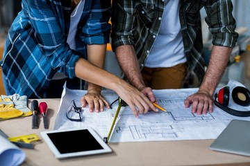 Male and female carpenters discussing on blueprint