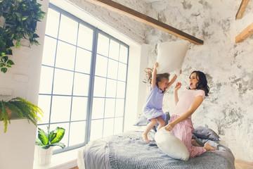 Mother and daughter pillow fight in bedroom