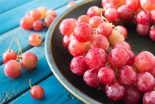 A plate of pink wet grapes macro