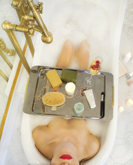 Attractive girl relaxing in the bath with tray of cosmetics