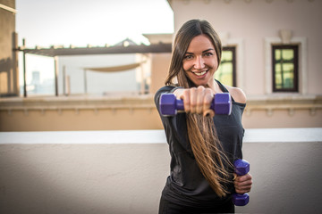 Portrait of smiling sporty girl holding weights outdoors.