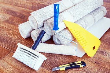Composition with various tools for home repair and rolls of wallpaper