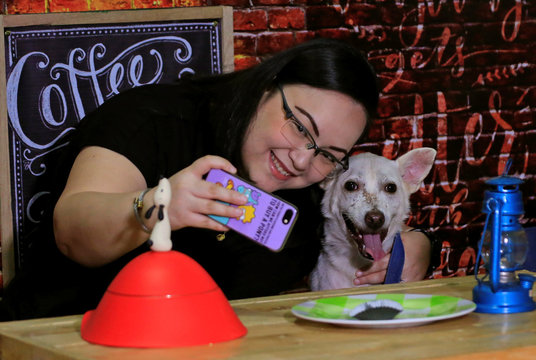 """A pet lover takes a selfie with a shelter dog during a """"Date with Dogs"""", inside the Philippine Animal Welfare Society (PAWS) headquarters in Quezon city, metro Manila"""