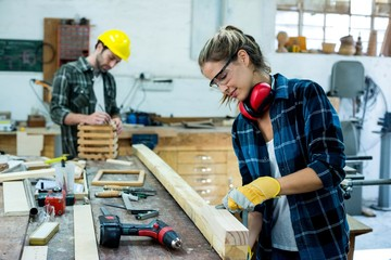 Male and female carpenters working in workshop