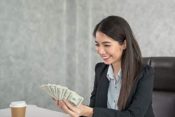 Asian business woman holding money in hand and smiling happy to business success.