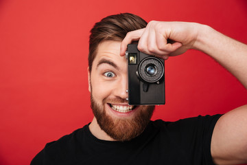 Portrait of smiling amateur male photographer making pictures using retro camera, isolated over red background