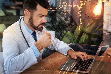 Medical worker. Clever progressive medical worker sitting at the table and drinking coffee while looking at the screen of his laptop and reading the newest article connected with his sphere of work