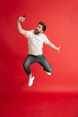 Bearded man jumping isolated using mobile phone make selfie.