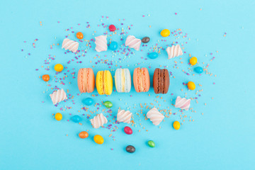 Macarons and sweets on a colored background. Festive mood
