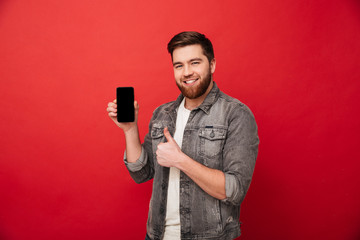 Image of unshaved happy man in denim presenting mobile phone on camera and showing thumb up, isolated over red background