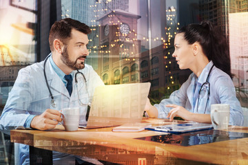Talking doctors. Calm bearded experienced doctor sitting in front of a modern laptop with a cup of coffee in his hand and looking at his young qualified colleague while having a conversation with her