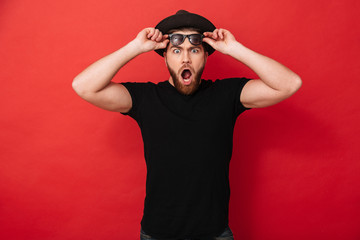 Portrait of surprised stylish man 30s in hat posing on camera and taking off black sunglasses, isolated over red background