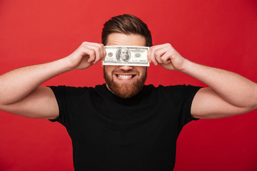 Photo close up of rich joyful man in black t-shirt demonstrating money prize while covering eyes with 100 dollar bill, isolated over red wall