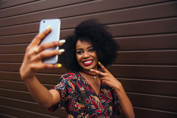 Cheerful beautiful afro-american girl taking a selfie on smartphone, showing a peace sign. Dressed in colorful blouse, with lush hairstyle.