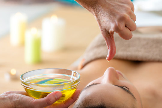 Aromatic oil dripping from finger at Ayurvedic massage.