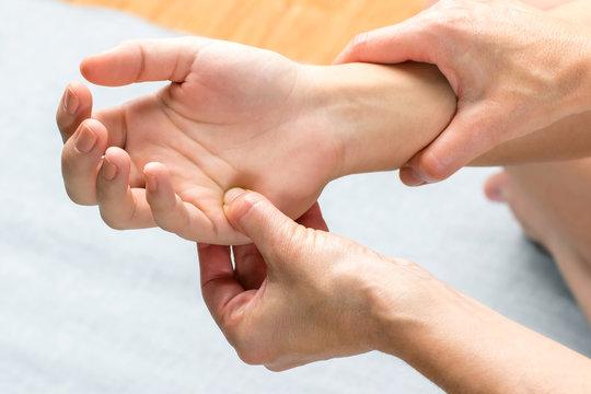 Chiropractor applying pressure on palm of female hand.