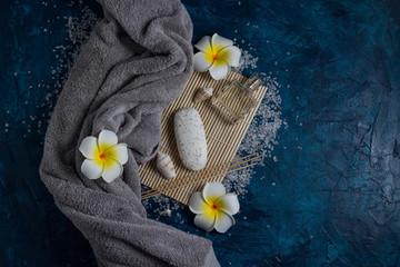 Acrylic Prints Spa concept. Towel, soap, Flower Hawaiian Plumeria, Sea salt on a blue background. Copy space. Flat lay, top view