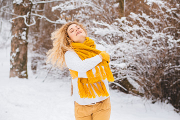 Happy winter fun curly blond woman in white sweater and yellow scarf relaxing in freedom enjoying the cold season. Winter mood concept.