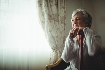 Thoughtful senior woman sitting on a chair