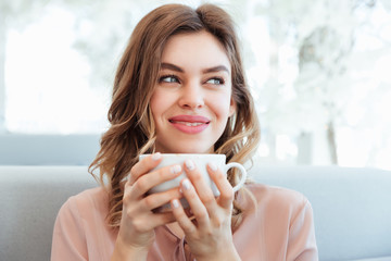 Portrait of a satisfied young woman holding cup of coffee