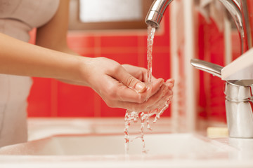 woman washes her hands on the faucet in the bathroom