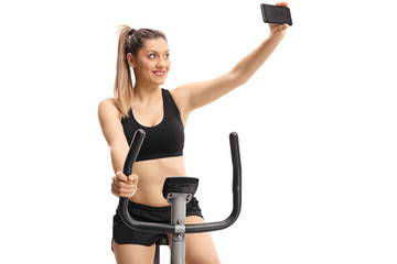 Young woman exercising on a cross-trainer machine and taking a selfie