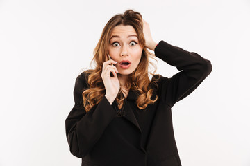 Picture of attractive woman with long curly hair in black outfit being surprised and grabbing head while having mobile call, isolated over white background
