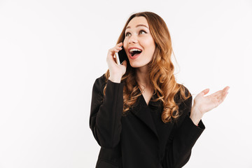 Adorable smiling woman with trendy hairstyle in black jacket talking on mobile phone and having pleasant conversation, isolated over white background