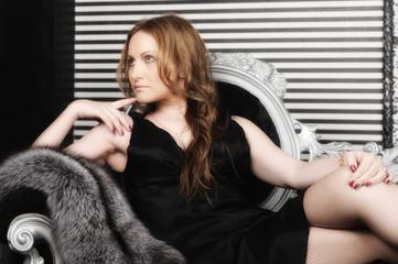 elegant woman in a black dress sitting on the sofa