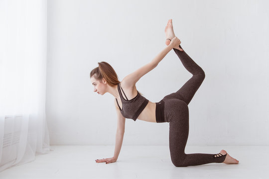 Fit young Caucasian woman practicing yoga at home standing in cat and cow pose arching her back. Raise your leg above your head. Lifestyle.