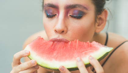 Girl with makeup face and red melon