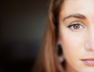 Half face of beautiful girl with make up and nose piercing.