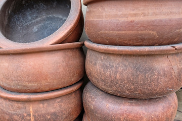 Handmade big clay casseroles stacked in front of the wall