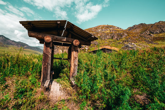 Wide-angle shooting of wooden shaft well in mountains surrounded by cannabis and fleabane native grasses with hill ridge and valley behind; view of abandoned dug well on a sunny summer day, Altai