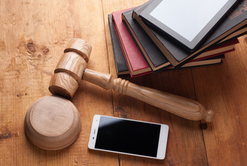 smartphone, the judge's gavel on wooden background.